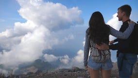 Pares novos de turistas que estão na parte superior da montanha e que olham a paisagem bonita para a frente eles Retrato do homem filme