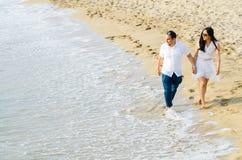 Pares novos descalços que andam em conjunto ao longo de uma praia na borda da ressaca foto de stock