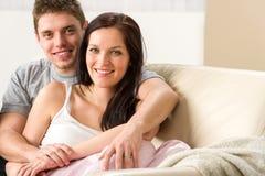 Pares novos despreocupados que abraçam no sofá Fotografia de Stock Royalty Free