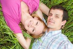 Pares novos do amor na grama Imagem de Stock Royalty Free