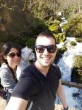 Pares novos do amor na montanha em um fundo da cachoeira Imagem de Stock