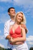 Pares novos do amor que sorriem sob o céu azul Imagens de Stock