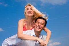 Pares novos do amor que sorriem sob o céu azul Fotografia de Stock