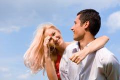 Pares novos do amor que sorriem sob o céu azul Imagem de Stock Royalty Free