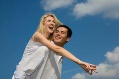 Pares novos do amor que sorriem sob o céu azul Fotos de Stock Royalty Free