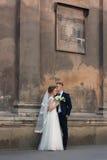 Pares novos do casamento que estão perto de uma parede velha bonita Fotos de Stock Royalty Free