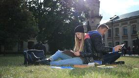 Pares novos do estudante que estudam no gramado do parque video estoque
