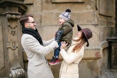 Pares novos do moderno com as ruas velhas de passeio da cidade do bebê imagem de stock royalty free