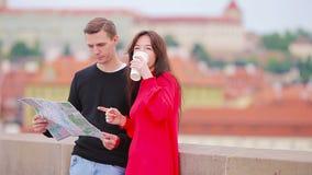 Pares novos do turista que viajam em feriados no sorriso de Europa feliz Fam?lia caucasiano com o mapa da cidade ? procura de video estoque