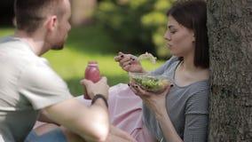 Pares novos do vegetariano que comem a salada e que bebem o assento do batido no parque vídeos de arquivo