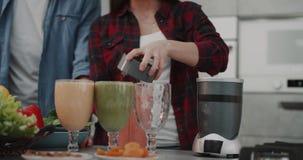 Pares novos do vegetariano que fazem o batido para toda a família na mulher da manhã que derrama o batido dentro a um vidro grand vídeos de arquivo