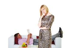 Pares novos, dona de casa e marido preguiçoso no sofá fotos de stock
