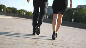 Pares novos dos executivos masculinos e fêmeas que andam na rua da cidade Homem de negócios e mulher de negócios que vão exterior vídeos de arquivo