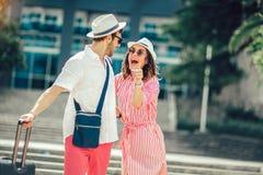 Pares novos dos viajantes que procuram o hotel imagem de stock royalty free