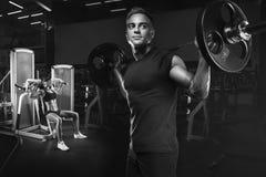Pares novos e aptos no gym que faz o exercício Imagens de Stock