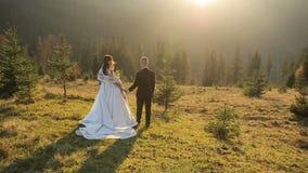 Pares novos e bonitos do casamento junto na inclinação das montanhas no por do sol Noivo e noiva bonitos ventoso vídeos de arquivo