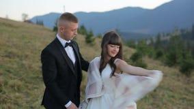 Pares novos e bonitos do casamento junto na inclinação do mountainat no por do sol Noivo e noiva bonitos ventoso video estoque