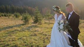 Pares novos e bonitos do casamento junto na inclinação do mountainat no por do sol Noivo e noiva bonitos ventoso vídeos de arquivo