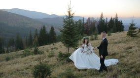 Pares novos e bonitos do casamento junto na inclinação do mountainat no por do sol Noivo e noiva bonitos ventoso filme