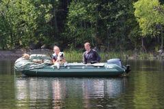 Pares novos e um animal de estimação em um barco de motor Cumprimente o fim de semana imagem de stock
