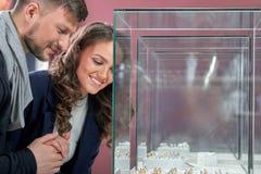 Pares novos em anéis de compra do amor na ourivesaria Imagens de Stock