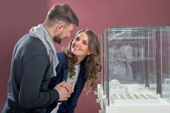 Pares novos em anéis de compra do amor na ourivesaria Imagem de Stock