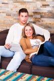 Pares novos em casa, lendo um livro e com uma tabuleta, sorrindo Imagem de Stock Royalty Free