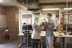 Pares novos em notas interiores da escrita do escritório moderno em etiquetas Foto de Stock Royalty Free