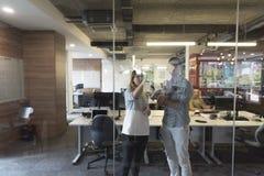 Pares novos em notas interiores da escrita do escritório moderno em etiquetas Fotos de Stock Royalty Free