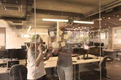 Pares novos em notas interiores da escrita do escritório moderno em etiquetas Imagens de Stock Royalty Free