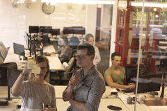 Pares novos em notas interiores da escrita do escritório moderno em etiquetas Fotografia de Stock Royalty Free