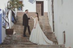 Pares novos em seu dia do casamento, em uma grande escadaria fotos de stock