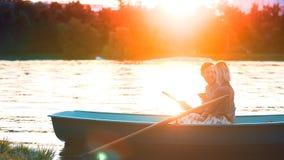 Pares novos em um barco na luz solar fotos de stock