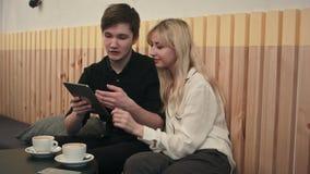Pares novos em um café, em um café bebendo e em usar a tabuleta digital vídeos de arquivo