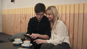 Pares novos em um café, em um café bebendo e em usar a tabuleta digital Fotos de Stock