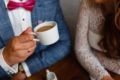 Pares novos em um café no café e no chá bebendo do sótão, sentando-se Café da manhã da manhã no hotel Imagem colhida dos pares em Foto de Stock Royalty Free