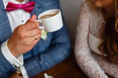 Pares novos em um café no café e no chá bebendo do sótão, sentando-se Café da manhã da manhã no hotel Imagem colhida dos pares em Imagem de Stock Royalty Free