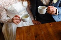 Pares novos em um café no café e no chá bebendo do sótão, sentando-se Café da manhã da manhã no hotel Imagem colhida dos pares em Fotos de Stock