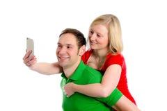 Pares novos em um selfie da tomada do abraço Fotografia de Stock