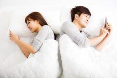 Pares novos em uma cama com telefones espertos Imagens de Stock Royalty Free