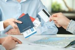 Pares novos em uma comunicação da agência da excursão com um close-up de viagem do pagamento com cartão de crédito do conceito do foto de stock royalty free