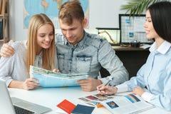 Pares novos em uma comunicação da agência da excursão com um conceito de viagem do agente de viagens que guarda a brochura fotos de stock royalty free