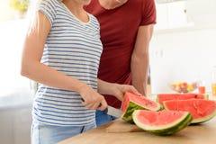 Pares novos em uma cozinha que corta a melancia vermelha Pares em sua cozinha branca contemporânea Imagem de Stock Royalty Free