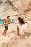 Pares novos em uma praia com naufrágio Foto de Stock Royalty Free