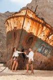 Pares novos em uma praia com naufrágio fotografia de stock