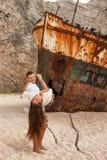 Pares novos em uma praia com naufrágio fotos de stock