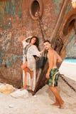 Pares novos em uma praia com naufrágio fotografia de stock royalty free