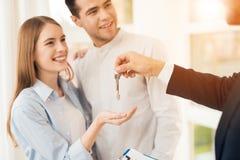 Pares novos em uma reunião com um corretor de imóveis O indivíduo e a menina fazem um contrato com propriedade de compra do corre imagens de stock