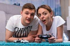 Pares novos emocionais que encontram-se em um tapete e que jogam jogos de vídeo Fotografia de Stock