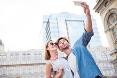 Pares novos engraçados dos turistas em uma caminhada imagens de stock
